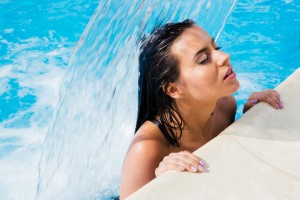 Beautiful woman standing in swimming pool under the waterfall